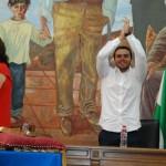 Ezequiel Carnero aplaudiendo los coros de ¡Sí se puede! al fondo del auditorio.